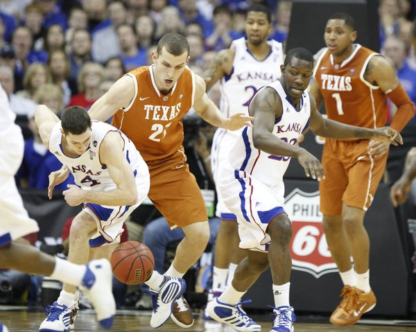 Kansas players Tyrel Reed and Mario Little go after a loose ball with Texas forward Matt Hill during the first half on Friday, March 11, 2011 at the Sprint Center.