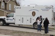 Residents in the area of the 700 block of Michigan Street visit as Lawrence police investigate the scene where a dead body was discovered Sunday afternoon in a creek bed and wooded area just east of Hawk's Pointe Apartments I and some nearby townhouses. In the background is a police investigation support van.