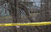 Lawrence police investigate the area where a dead body was discovered Sunday afternoon in a creek bed and wooded area in the 700 block of Michigan Street near Hawk's Pointe I Apartments.