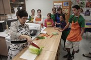 West Junior High School family and consumer science teacher Kerri Hess demonstrates how to chop up a cabbage during a Foods 2 class March 16 at the school.