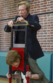 Lawrence magician Gene Kean performs some magic with a guillotine on principal Jeanne Fridell at Woodlawn School.