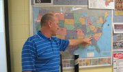 Stacy Reed stands in front of a United States map in his classroom that shows each location he's traveled to watch basketball.