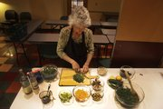 "Hilary Kass prepares some veggies for a kale salad, as she gets ready to teach a class called ""Eat Your Greens!"" at The Merc on March 17."