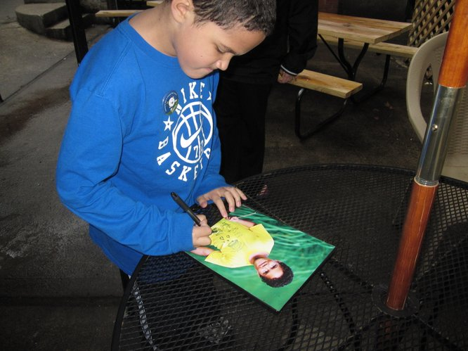 Eight-year-old Isaac Greenly, a student at Deerfield School, signs autographs a picture for Trevor LaFarge, who organized Lawrence's first St. Baldrick's Foundation fundraiser, which raises money for childhood cancer research. Isaac is a cancer survivor.
