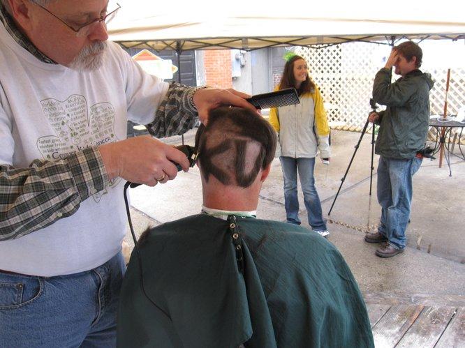 Barber Jim McDaniel shaves a K-U on the back of Trevor LaFarge's head.