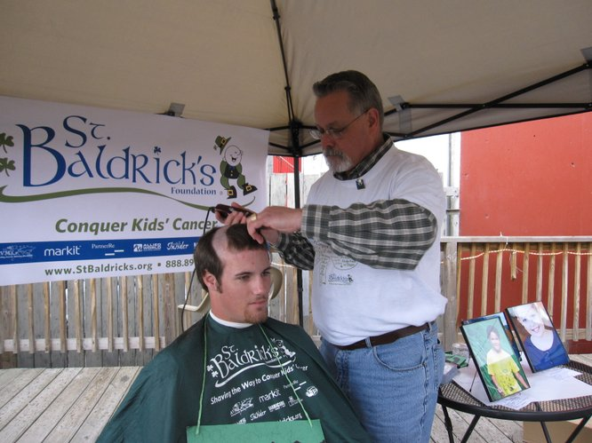 Barber Jim McDaniel, of Rossville, shaves the head of Trevor LaFarge during the St. Baldrick's Foundation fundraiser in Lawrence.