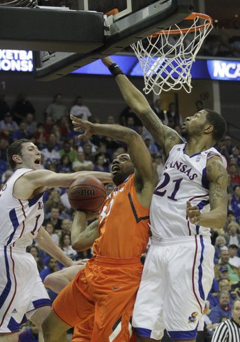 Kansas players Tyrel Reed, left, and Markieff Morris defend Illinois&#39; Demetri McCamey (32) Sunday, March 20, 2011 at the BOK Center in Tulsa, Okla.