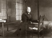 Temperance leader Carrie Amelia Nation, shown with her bible kneeling in prayer by a chair in a jail cell at an unknown location.