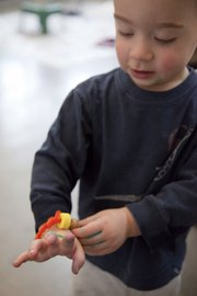 Gavin Koonce, 2, puts on a bracelet he made in art class with the Lawrence Arts Center preschool.