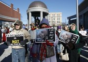 Demonstrators stand with signs outside the New Jersey Statehouse in Trenton during an anti-abortion rally Monday, Jan. 24, 2011. The rally was one of many around the country held by abortion opponents on the 38th anniversary of Roe v. Wade, the landmark U.S. Supreme Court decision that legalized abortion. Bills by the dozen are advancing through statehouses nationwide that would put an array of new obstacles — legal, financial and psychological — in the path of women seeking abortions.
