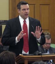 Kansas Secretary of State Kris Kobach discusses election fraud issues during a state Senate Ethics and Elections Committee meeting, Thursday, March 17, 2011, at the Statehouse in Topeka. Kobach is pushing proposals to require voters to show photo identification at the polls and to require people registering to vote for the first time in Kansas to prove they're citizens.