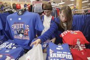 As the Kansas University men's basketball team prepares to play in the NCAA Sweet 16 in San Antonio, Imy Poteet, Perry, left, and her granddaughter Caitlin Schlesener, 13, Lawrence, picked out their Jayhawks shirts Thursday at Kansas Sampler, 921 Mass. The store said that in the last few days they've sold more than 300 T-shirts and some styles have sold out.
