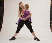 Erin Brown in the starting position for a pile squat using her daughter, Lola, 2, as resistance.