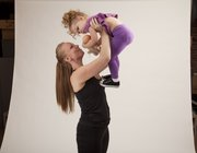 Erin Brown does a modified chest press using her daughter, Lola, 2, as resistance. Start by holding your child close to your chest and then push him or her up and outwards, working both the chest and the shoulders. Then pull the child back in and return to the starting position. Do as many reps as your child will allow.