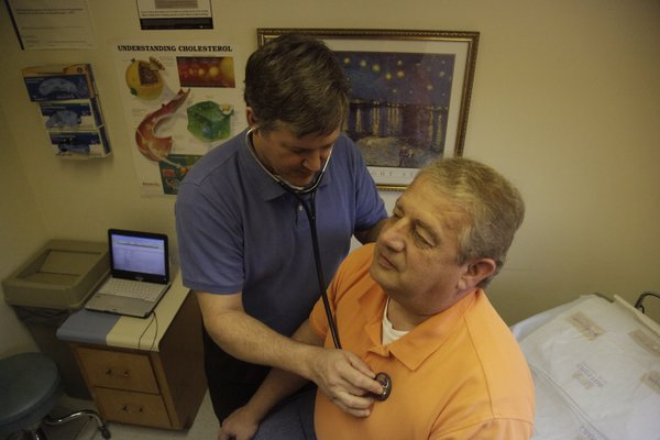 Daniel Dickerson gives George Hensler, of Overland Park, a checkup at his office at Eudora Family Care Friday, March 25, 2011. Dickerson says prevention  including regular checkups  is key for both patients&#39; health and also their pocketbooks.