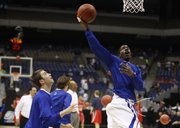 Kansas guard Tyshawn Taylor hooks in a shot prior to tipoff against Richmond on Friday, March 25, 2011 at the Alamodome in San Antonio. At left is KU guard Brady Morningstar.