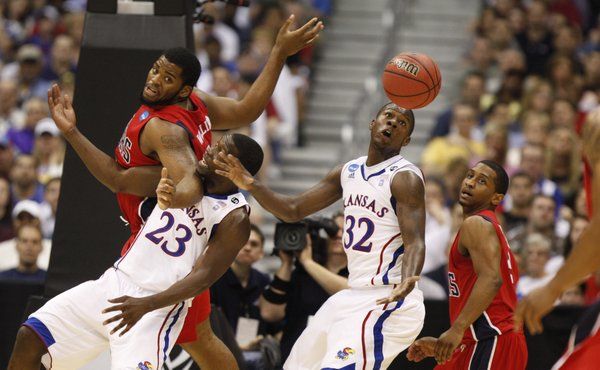 Kansas players Mario Little (23) and Josh Selby (32) wrestle for a loose ball with Richmond players Derrick Williams, left, and Cedrick Lindsay during the first half on Friday, March 25, 2011 at the Alamodome in San Antonio.