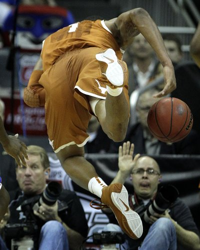 Texas forward Gary Johnson (1) dives into a row of photographers as he tries to keep a ball in bounds during the first half of an NCAA college basketball game against Kansas for the championship of the Big 12 men's basketball tournament Saturday, March 12, 2011 in Kansas City, Mo. (AP Photo/Charlie Riedel)