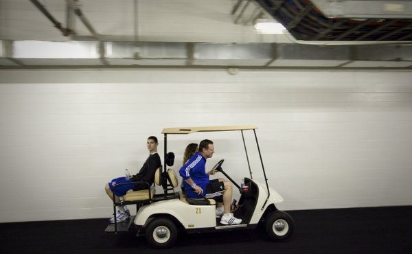 Kansas head coach Bill Self and Tyrel Reed are escorted to press conferences on a golf cart on Saturday, March 26, 2011 at the Alamodome in San Antonio.