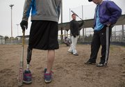Trevor Roberts, left, holds his bat at his side as he waits his turn to swing after McLouth teammate Wyatt Farris, center.