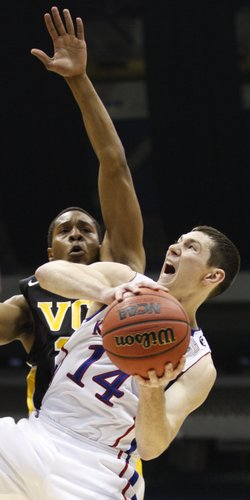 Kansas guard Tyrel Reed attempts a shot under the outstretched arm of Virginia Commonwealth guard Bradford Burgess during the first half on Sunday, March 27, 2011 at the Alamodome in San Antonio.
