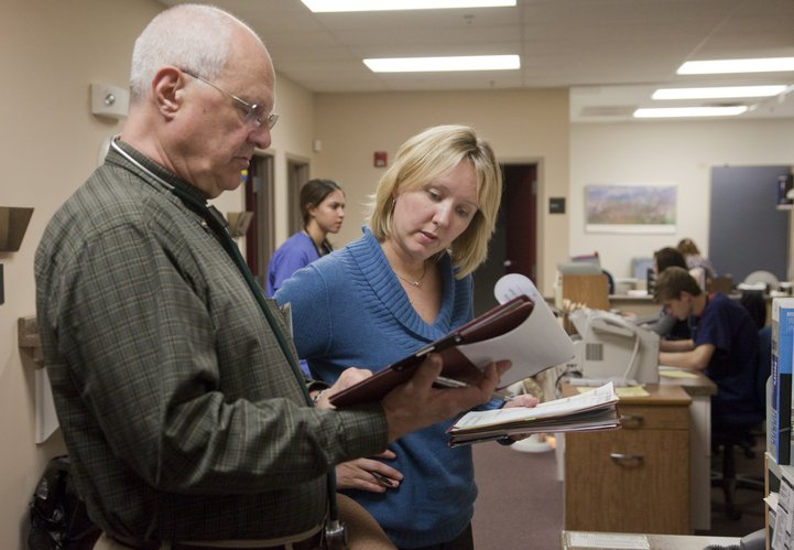 Dr. John Listerman, left and Allison Veeder, ARNP, confer about a patient Wednesday, March 30, 2011, at Heartland Community Health Center. The center provides medical care for low-income residents.