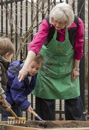 Linda Reimond gives instructions to children in the garden area at the Lawrence Arts Center. Reimond is director of the center's preschool program.