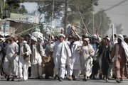 Afghan protesters walk with sticks Saturday as they carry a wounded colleague during a demonstration to condemn the burning of a copy of the Muslim holy book by a U.S. Florida pastor, in Kandahar southern of Afghanistan.