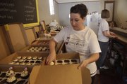 Cami SanRomani fills an order at her shop in downtown Lawrence, Cami's Cake Co., during The Great American Bake Sale, a charity event with proceeds going to Share Our Strength.