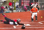 Lawrence High's Kasey Waite slides around Shawnee Mission Northwest catcher Cierra Carbajo for a score during Lawrence High's game against Shawnee Mission Northwest Saturday, April 2, 2011 at LHS.