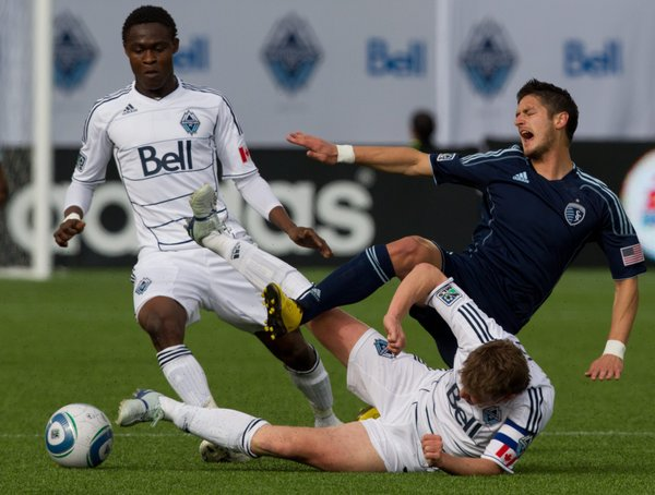 Vancouver Whitecaps' Terry Dunfield, bottom, tackles Sporting Kansas City's Milos Stojcev, top right, as Vancouver's Gershon Koffie, left, looks on during the first half of an MLS soccer game in Vancouver, British Columbia, on Saturday, April 2, 2011.