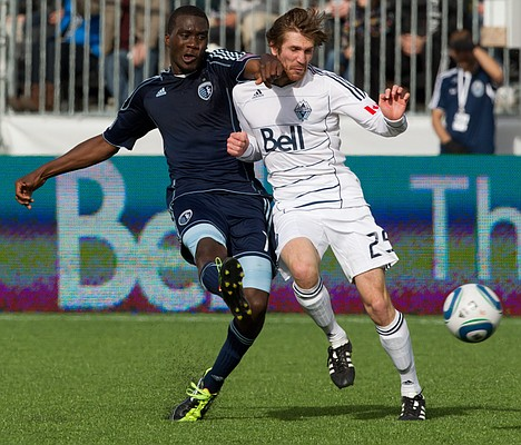 Sporting Kansas City's C.J. Sapong, left, plays the ball past Vancouver Whitecaps' Jonathan Leathers during the first half of an MLS soccer game in Vancouver, British Columbia, on Saturday, April 2, 2011.