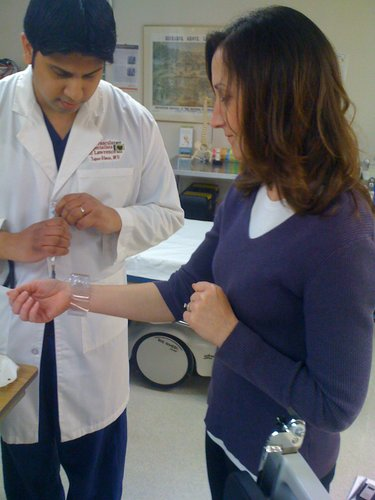 """Dr. Tapas """"Joey"""" Ghose, of Cardiovascular Specialists of Lawrence, shows WellCommons editor Karrey Britt how a wrist band is used to control bleeding after a diagnostic heart test  is done through the wrist. The wrist band has an air pump that applies pressure based on need. He demonstrated the technology Friday, April 1, 2011, at Lawrence Memorial Hospital."""