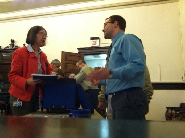 Workers accept ballot boxes in the commission meeting room upstairs at the Douglas County Courthouse, 1100 Mass. Election worker Carrie Moore talks with Phillip Wrigley, right, who was supervising poll judge in Wakarusa Township, north of Lawrence.