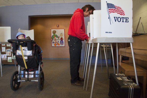 Jay Hester, right, marks his selections on his ballot while his son Oliver, 14 months, waited behind him on Tuesday, April 5, 2011, at New York Elementary School.