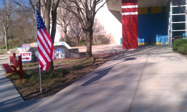 An American flag and a voting sign greeted those who were headed to the polls at the East Lawrence Reaction Center Tuesday, April 5, 2011. Though volunteers were ready inside with a large stack of ballots, by 9:30 just 14 ballots had been cast there.