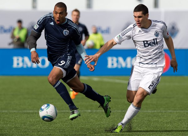 Sporting Kansas City's Teal Bunbury, left, carries the ball past Vancouver Whitecaps' Michael Boxall during the first half of an MLS soccer game in Vancouver, British Columbia, on Saturday, April 2, 2011.
