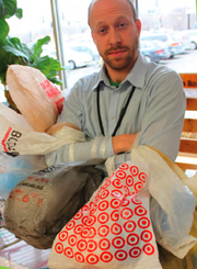 Brian Phillips, store operations manager at The Merc, stands with a collection of 60 plastic bags, the average number of bags a family of four gathers in one month. At the request of the food cooperative's owners, the store will no longer offer plastic bags for packing groceries.