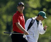 Former Kansas University golfer Gary Woodland reacts after hitting a shot on the 12th hole during a practice round for the Masters on Wednesday in Augusta, Ga. At right is caddie Jon Yarbrough. Woodland, a Topeka native who earned a spot in the Masters field by winning the Transitions in Orlando, Fla., last month, tees off in the last group at 12:59 p.m. today, one group behind favorite Phil Mickelson. Woodland is grouped with Jhonattan Vegas of Venezuela, to whom he lost a playoff in the Bob Hope Classic, and Alvar Quiros of Spain. That same threesome tees off at 10:41 a.m. in Friday's second round.