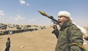 A Libyan rebel fighter, holding a rocket launcher, shouts religious slogans Friday after gunshots were heard as fellow comrades offer prayers in the background in Ajdabia, Libya. Rebel fighters sent scouts Friday toward the contested oil port of Brega to seek clues on whether pro-government forces took advantage of a mistaken NATO airstrike that pounded opposition tanks and sent survivors into retreat.