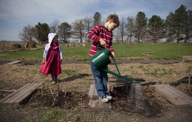 "Prairie Moon Waldorf School first-grader Angus Burke works to steady a watering can as he makes his way across the planks watering his classmate's gardens on Wednesday, April 6, 2011, at Prairie Moon Waldorf School. At left is first-grader Bella Paradis. Prairie Moon was named a ""2011 Kansas Green School of the Year"" by the Kansas Association for Conservation and Environmental Education."