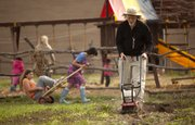 Rick Mitchell, one of the founders of Prairie Moon Waldorf School, works on tilling the garden while children play outside Wednesday, April 6, 2011, at the school.