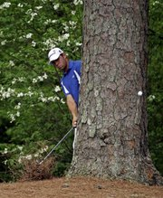 Gary Woodland hits from a tree on the 11th hole during the second round of the Masters. Woodland shot a second-round 73 on Friday at Augusta, Ga.