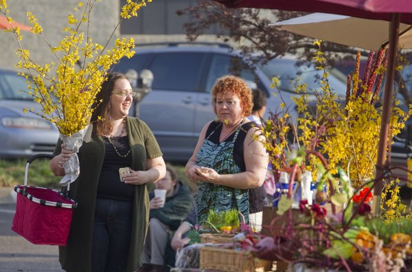 Beth McKeon, left, picks up a start of a forsythia bush from vendor Micky McKillip on the opening day of the 2011 Lawrence Farmers' Market.
