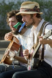 Thomas Montgomery, left, and Mikee Pruitt of 20,000 Strongmen, from Kansas City, Mo., perform on guitar, banjo and kazoo Saturday at the Lawrence Farmer's Market. This year marks the 35th anniversary for the community produce market.