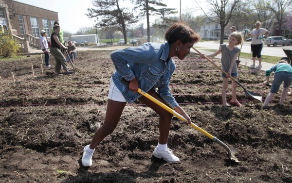 Dakota Collins helps dig up an expanded garden at Liberty Memorial Central Middle School on Saturday, April 9, 2011. Watkins Community Museum of History will be opening an exhibition Friday on the school's garden project.