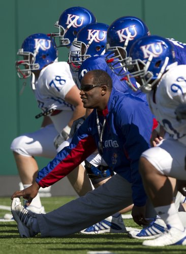 Kansas head coach Turner Gill stretches out with his players during practice on Monday, April 11, 2011 at the practice fields near Memorial Stadium.