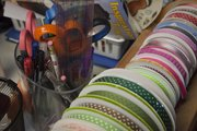 Rolls of color ribbon and other supplies are part of the tools Jamie Knabe uses for scrapbooking. After closing her scrapbook store down earlier this year, she now works out of her basement in her rural Douglas County home south of Eudora.