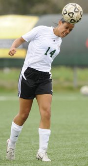 Free State's Margaux Gill hits a header against Shawnee Mission South on Thursday, April 14, 2011.
