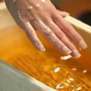 A Rejuvene Day Spa employee demonstrate the processes of a hand exfoliation treatment, which can involve applying a salt scrub, massaging the salt scrub,  performing a paraffin dip after rinsing the salt scrub from the hands, shown above, followed by a removal of the paraffin.